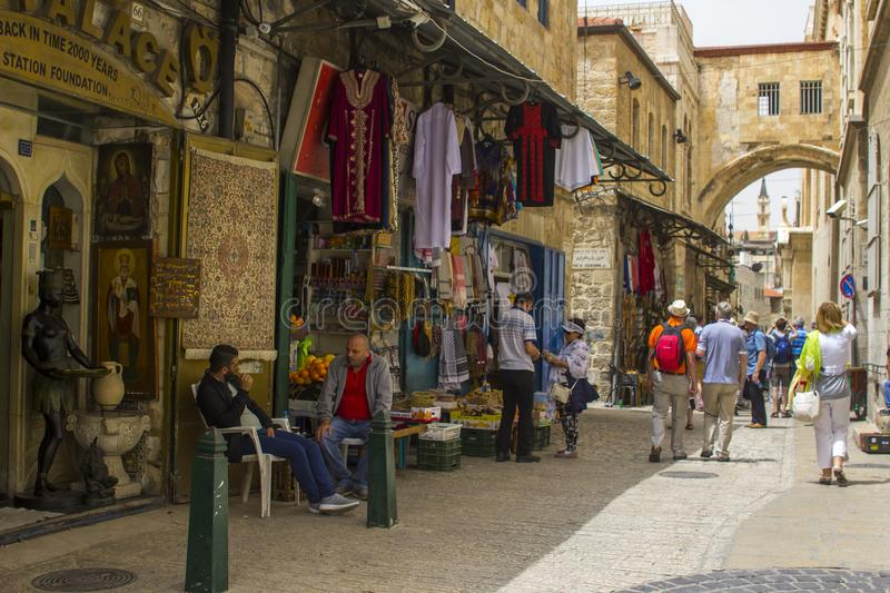 Tourist passing local men as they chat outside shop in Jerusalem. 10 May 2018 Tourist passing local men as they sit and chat outside a small shop in the walled royalty free stock image
