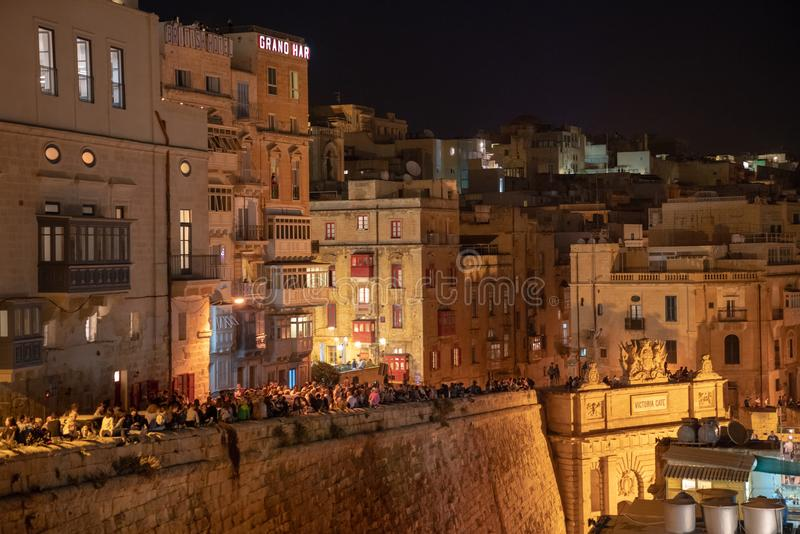 Beautiful old town of Valletta at night with many people crowded by the coastline watching live show and waiting for the fireworks. May 01, 2018. Valletta, Malta royalty free stock image