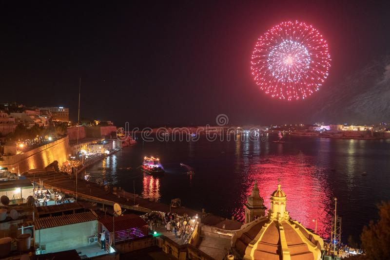 Beautiful old town of Valletta at night with many people crowded by the coastline watching live show and waiting for the fireworks. May 01, 2018. Valletta, Malta stock photos