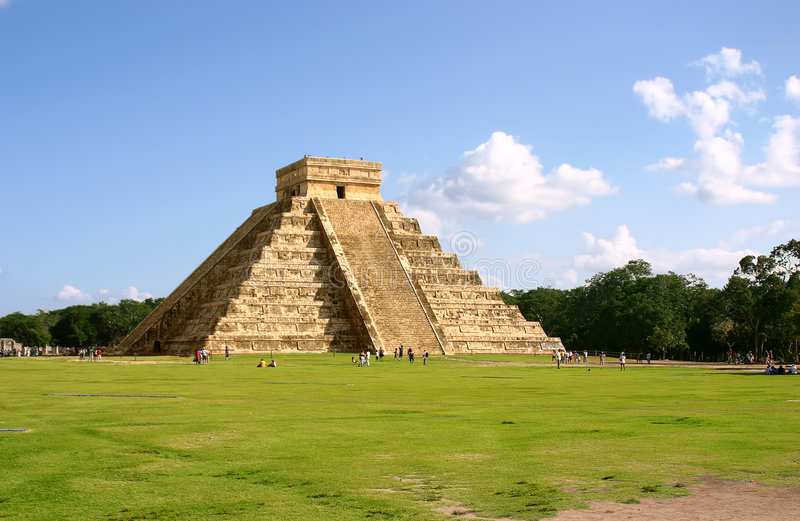 Maya pyramid. Antique mayan pyramid on green field over blue sky stock photo