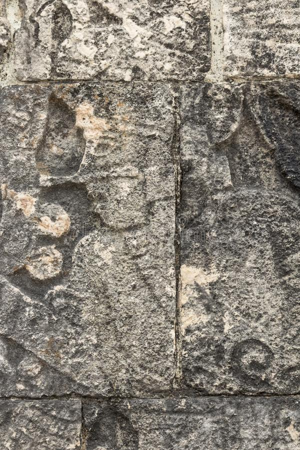 Mayan ball player. Sculpted on bas relief on the court wall. Detail on Chichen Itza stadium carved on stone. Players had feathered helmets and leather padding stock photos