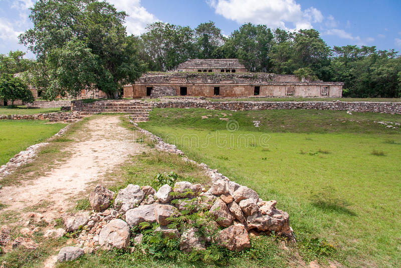 Mayan Complex in Labna Yucatan Mexico. A path to the ruins of the facade of a mayan stone building complex in front of a tropical jungle. The archaeological site stock photo