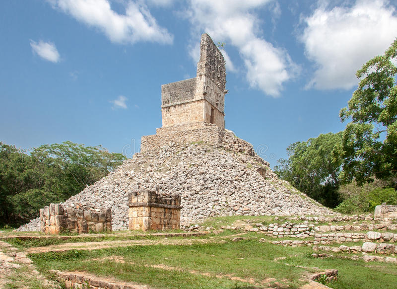 Mayan Temple in Labna Yucatan Mexico. The ruins of a mayan stone temple with its facade wall full of symbols on top of a pile of stones. The archaeological site stock photo