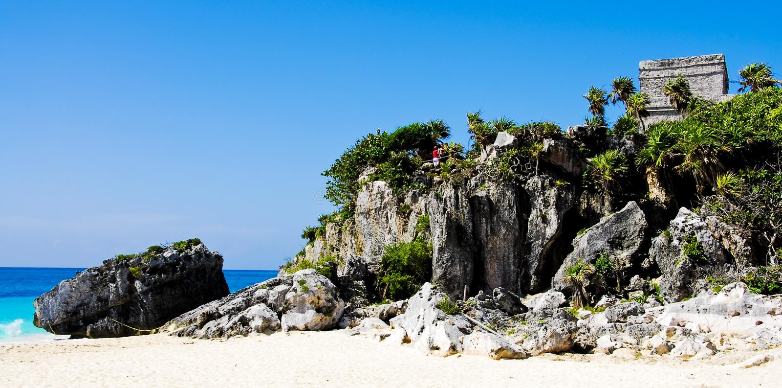 Mayan Tulum Ruins. Tulum Ruins in Mexico on the Beach. White sandy beach and crystal blue ocean with the ruins above on cliff royalty free stock photography