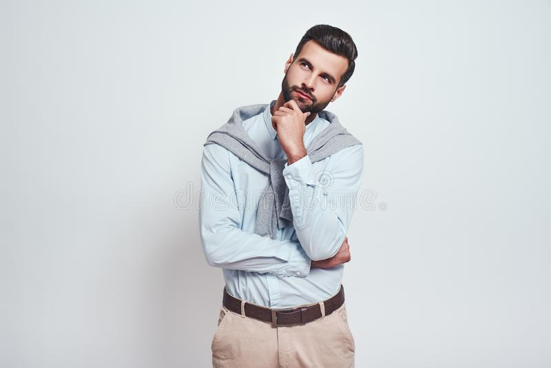 Maybe is...Charming young man with hand on chin thinking about question with thoughtful face while standing against grey stock photography