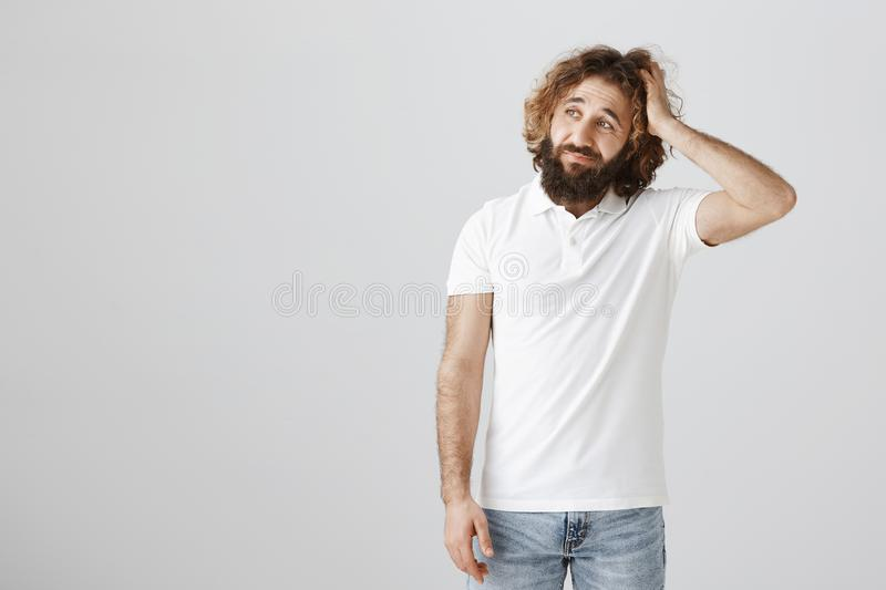 Maybe I should say sorry for my behaviour. Portrait of troubled attractive eastern male with curly hair and beard royalty free stock photo