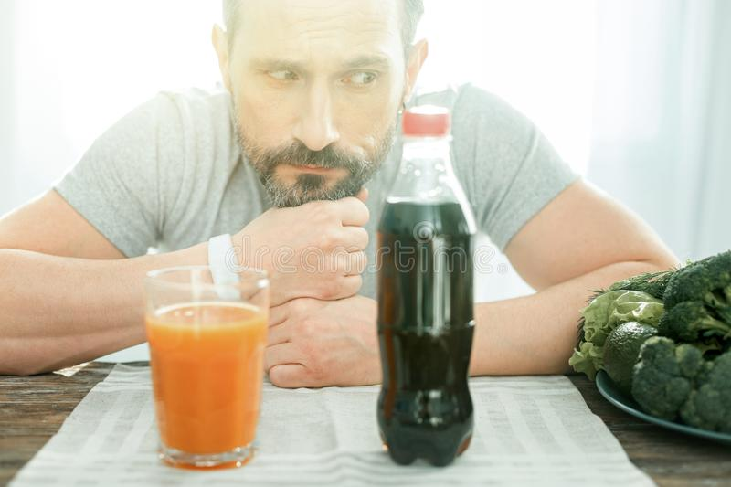 Deep confusing man sitting and looking at cola. Maybe try this. Deep confusing unshaken man sitting by the table putting chin on his hands and looking at the stock images