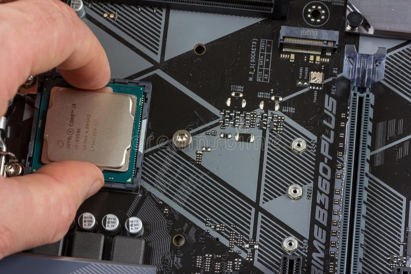 Man installs an 8th generation Intel core I3 processor into a motherboard socket royalty free stock photography