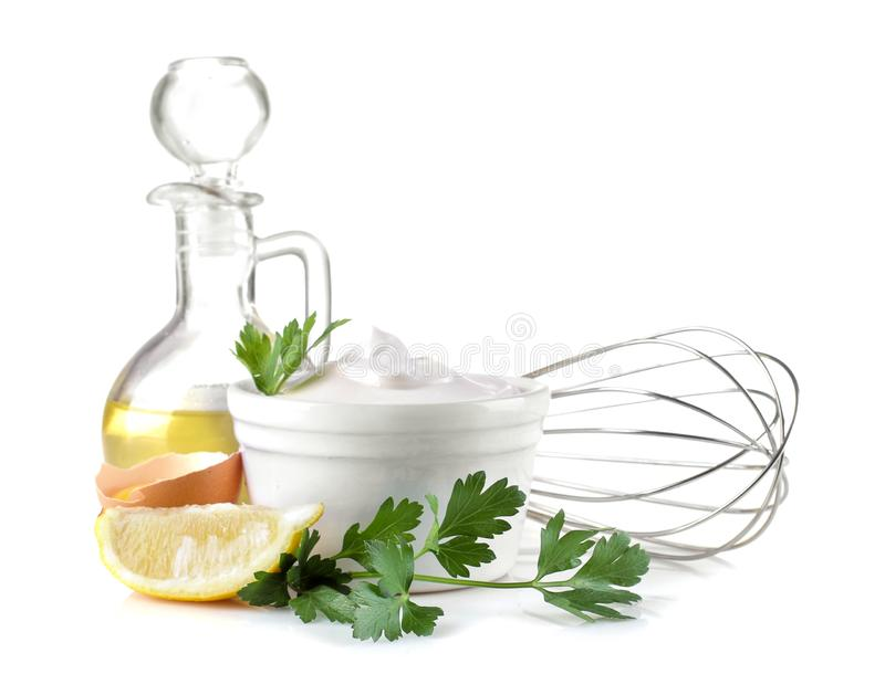 Mayonnaise in a ceramic bowl and ingredients for making sauce on a white isolated background. white sauce stock photos