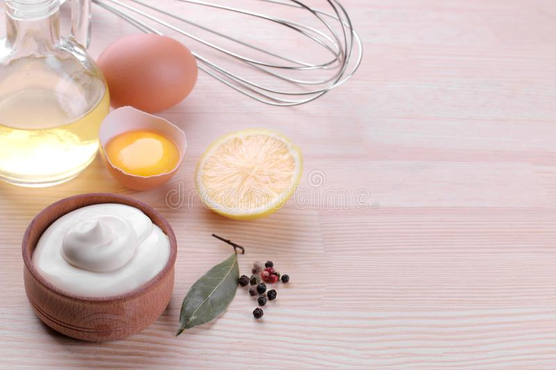 Mayonnaise in a wooden bowl and ingredients for making mayonnaise on a natural wooden background. white sauce. with space for text stock image