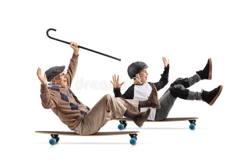Mayor alegre con un bastón que se sienta en un longboard y que monta con su nieto imagenes de archivo