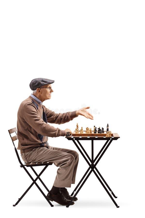 Mayor asentado en una tabla que juega el ajedrez y la discusión aislados en w fotos de archivo