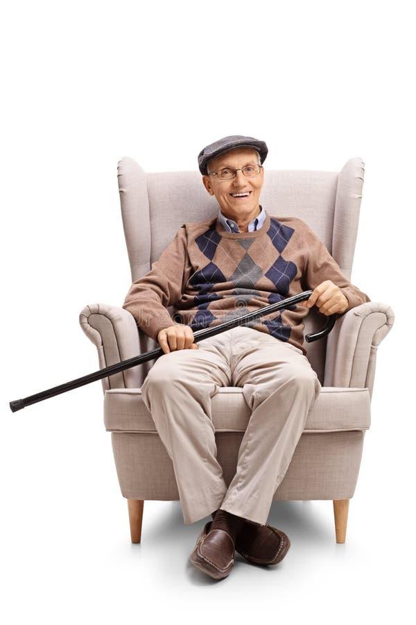 Mayor con un bastón que camina que se sienta en una butaca imagenes de archivo