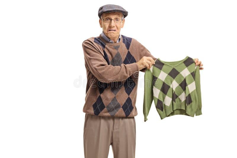 Mayor decepcionado que sostiene una blusa encogida fotografía de archivo libre de regalías
