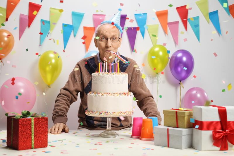 Mayor que celebra su cumpleaños con una torta y un cuerno del partido fotos de archivo libres de regalías