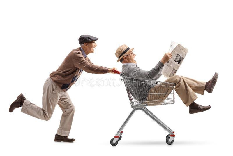 Mayor que empuja un carro de la compra con otro mayor con un newspa fotos de archivo libres de regalías