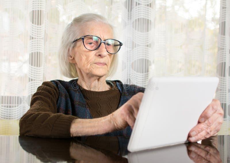 Mayor que usa el dispositivo de la tableta en casa imagenes de archivo