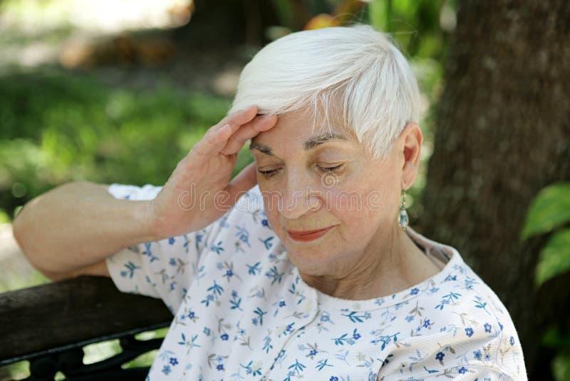 Mayor triste con dolor de cabeza foto de archivo