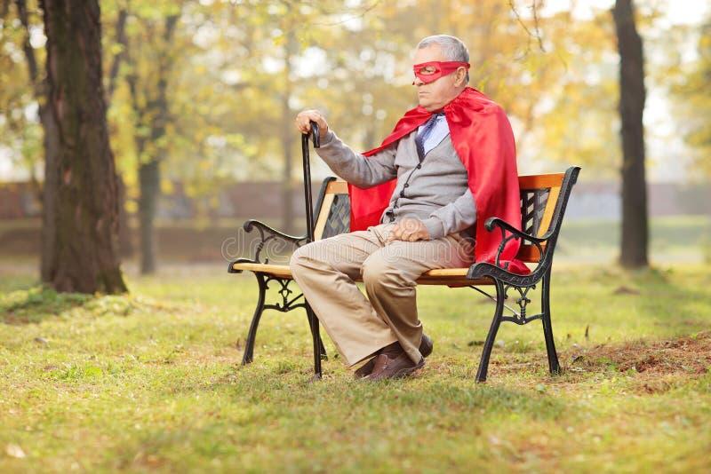 Mayor triste en el equipo del super héroe que se sienta en parque imágenes de archivo libres de regalías