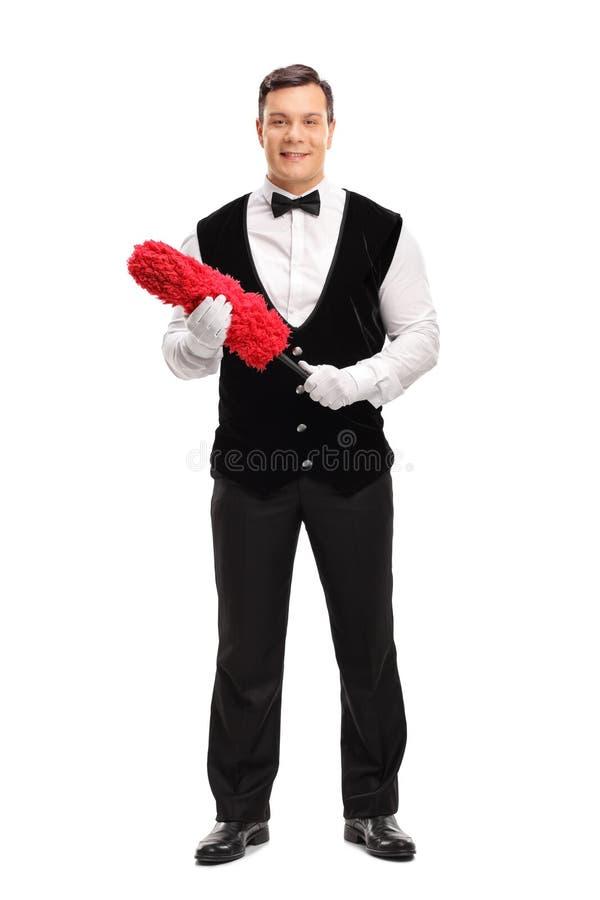 Mayordomo alegre que sostiene un plumero rojo foto de archivo libre de regalías
