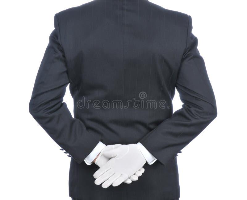Mayordomo con las manos detrás el suyo detrás imagenes de archivo