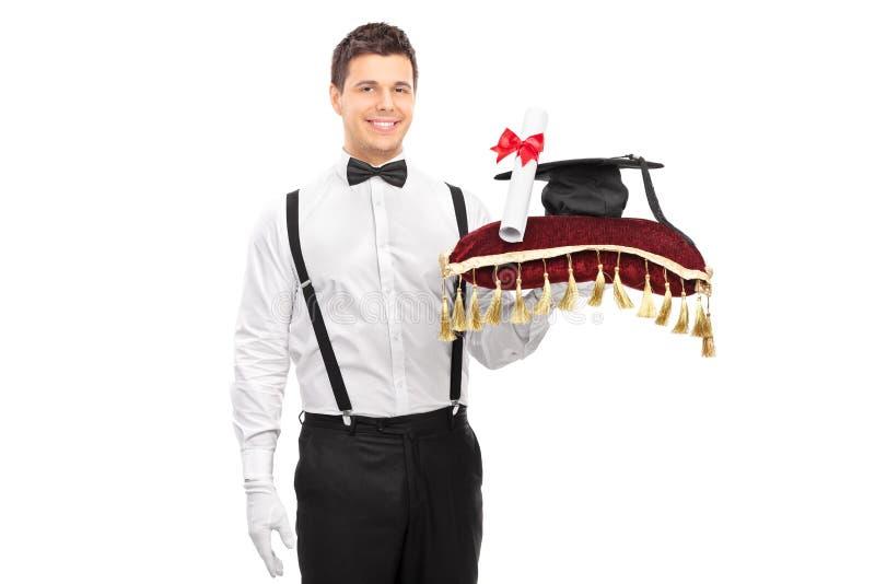 Mayordomo masculino que sostiene un diploma y un birrete imagenes de archivo