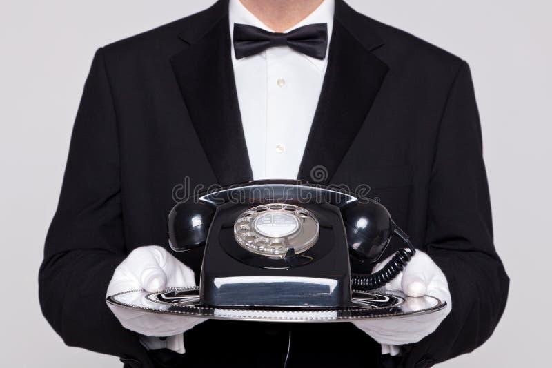 Mayordomo que sostiene un teléfono en la bandeja de plata imagen de archivo libre de regalías