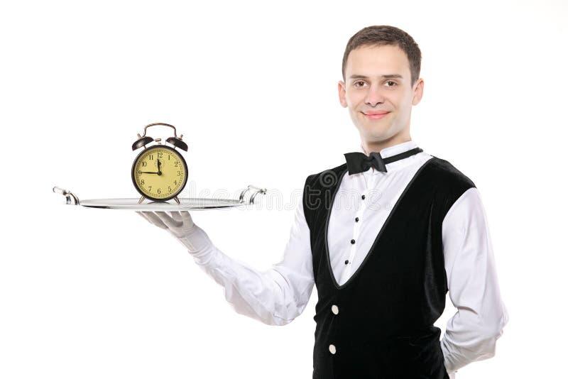 Mayordomo que sostiene una bandeja de plata con un reloj foto de archivo