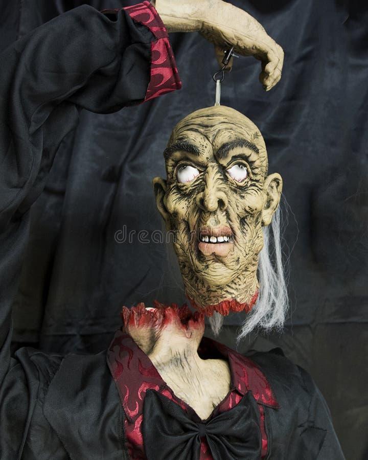Mayordomo sin cabeza que lleva a cabo su propia cabeza suspendida imagenes de archivo