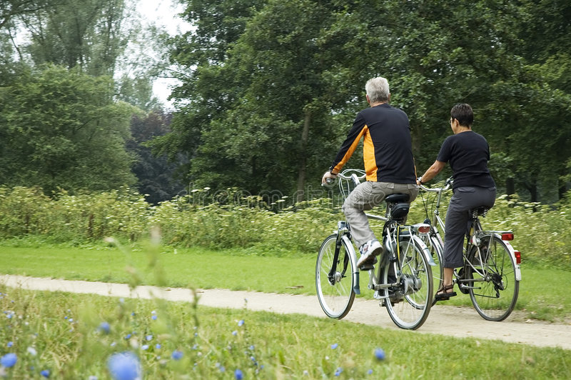 Mayores Biking en el parque imágenes de archivo libres de regalías