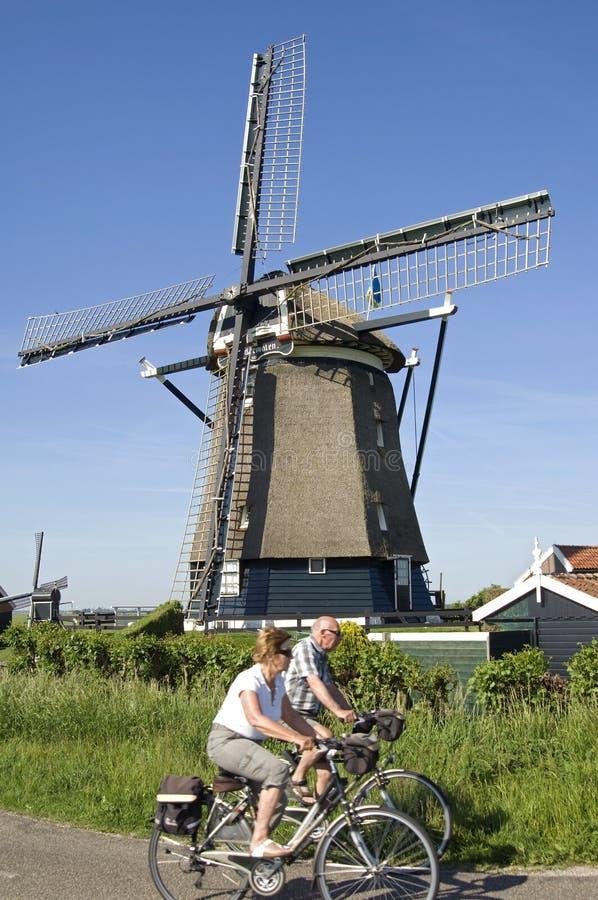 Mayores de ciclo y molino de viento histórico fotografía de archivo