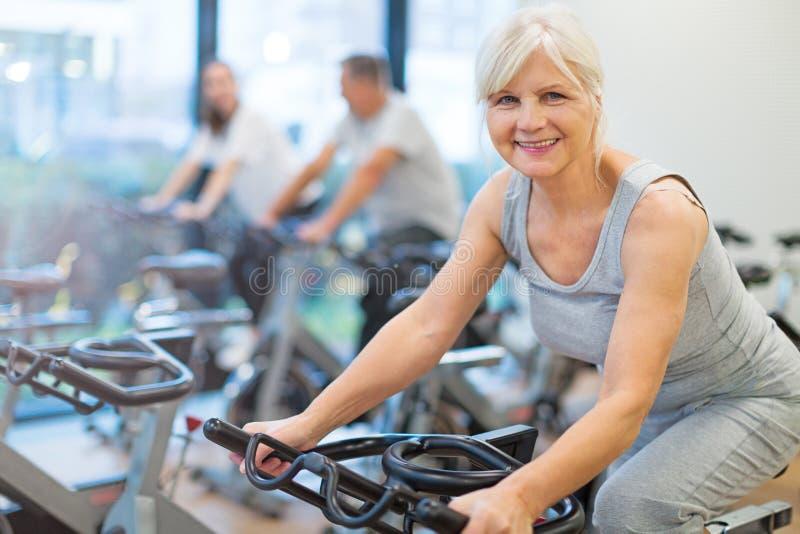 Mayores en las bicicletas estáticas en clase de giro en el gimnasio foto de archivo