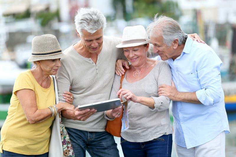 Mayores felices que viajan y que visitan usando la tableta foto de archivo