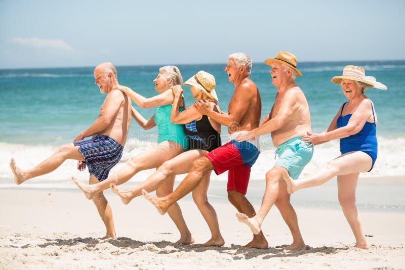 Mayores que bailan en fila en la playa imagenes de archivo