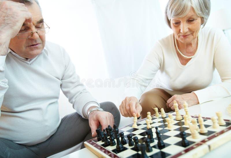 Mayores que juegan a ajedrez foto de archivo