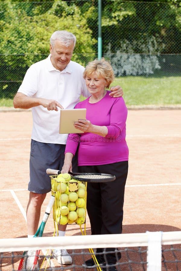 Mayores que juegan a tenis foto de archivo