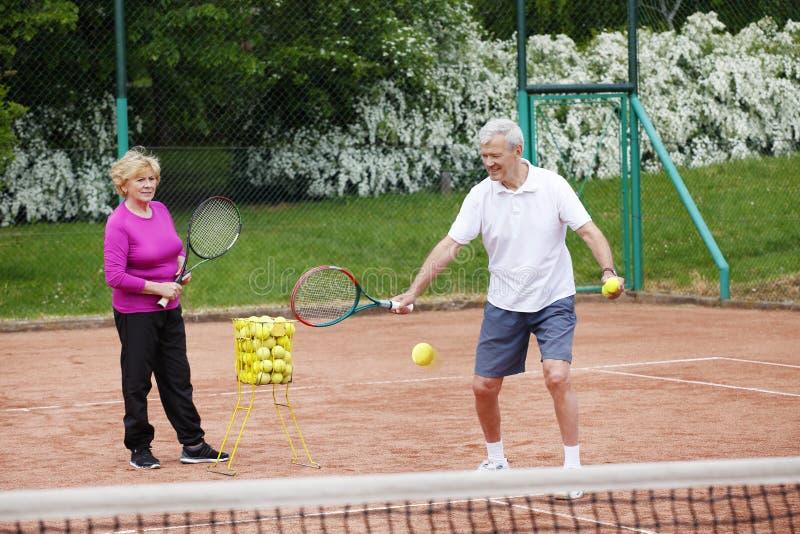 Mayores que juegan a tenis imágenes de archivo libres de regalías