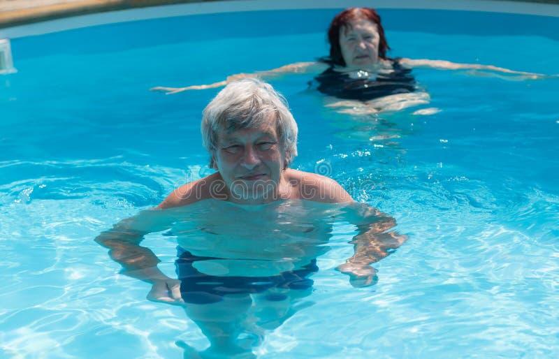 Mayores que nadan en una piscina fotografía de archivo