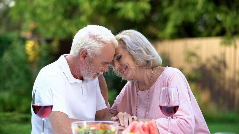Mayores que se sientan en la tabla y que recuerdan su vida junta, matrimonio feliz fotos de archivo libres de regalías