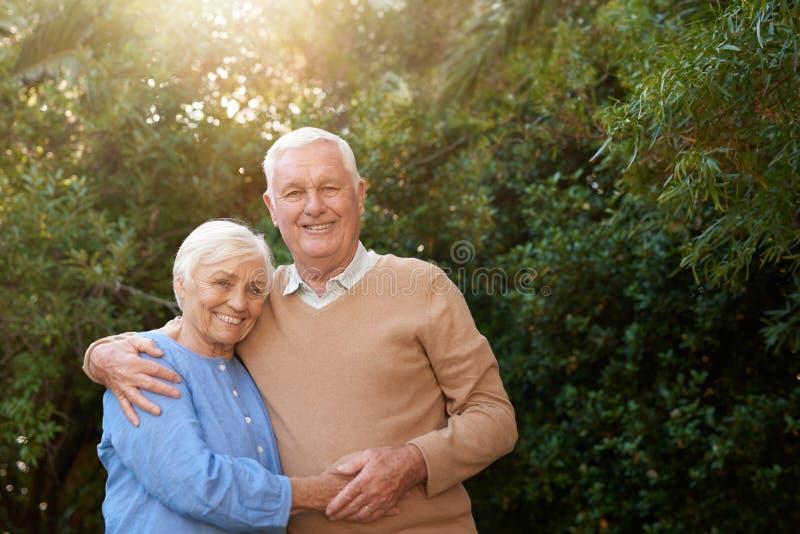 Mayores relajados que se unen y que sonríen en su patio trasero fotos de archivo libres de regalías