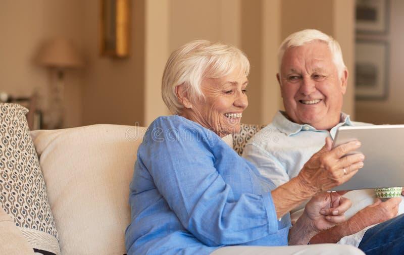 Mayores sonrientes que hojean Internet de su sofá de la sala de estar fotos de archivo libres de regalías