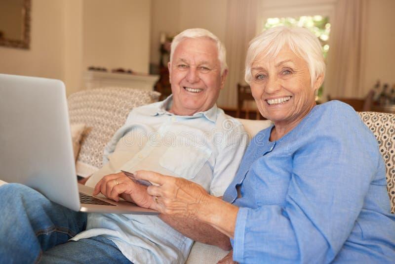 Mayores sonrientes que sientan en casa hacer compras en línea con un ordenador portátil fotos de archivo libres de regalías