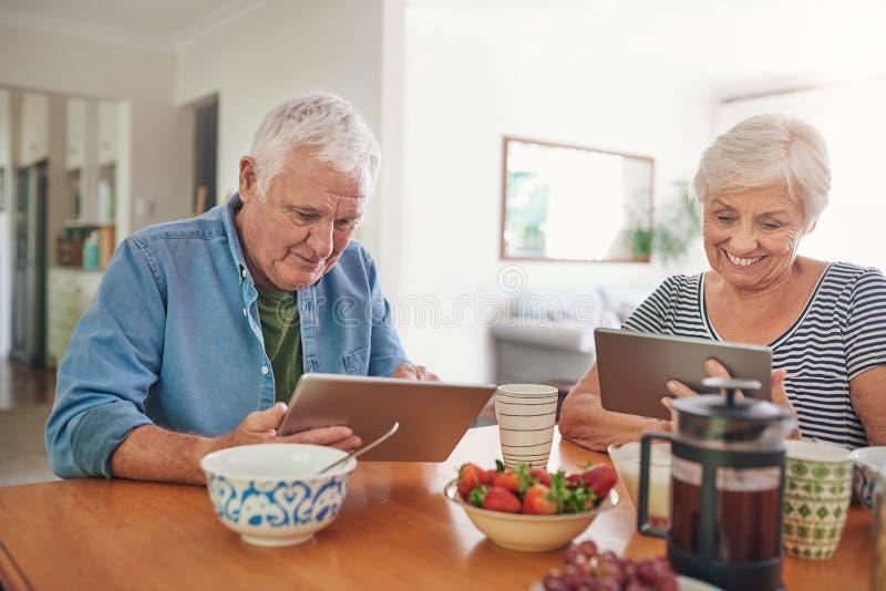 Mayores sonrientes que usan las tabletas digitales sobre el desayuno en casa imagenes de archivo