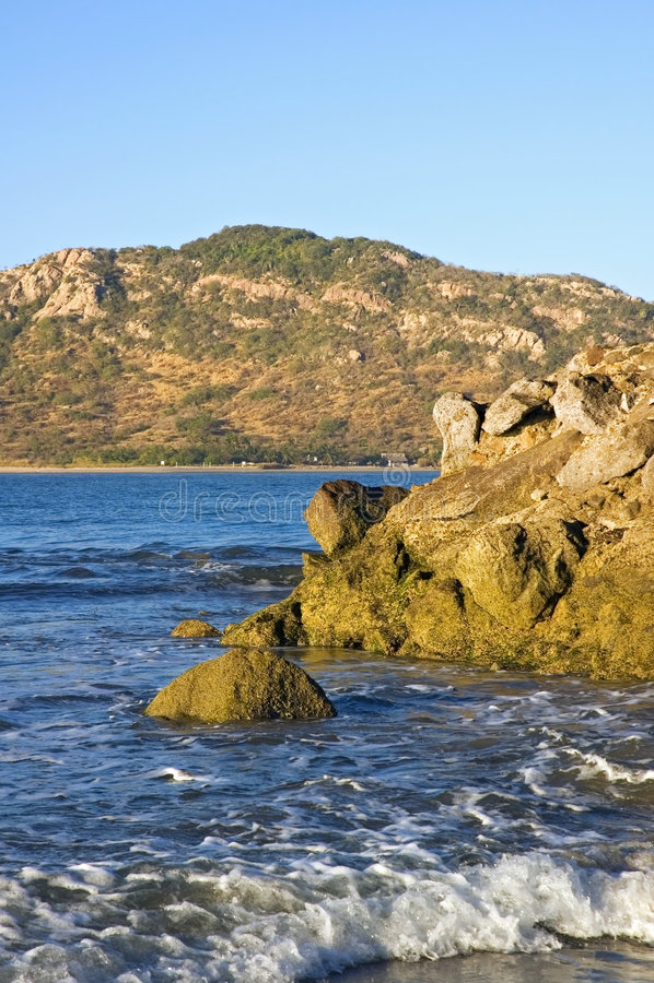 Mazatlan, Mexico Coast and Deer Island. Surf crashes on beach of Mazatlan Mexico - Deer Island in distance stock image