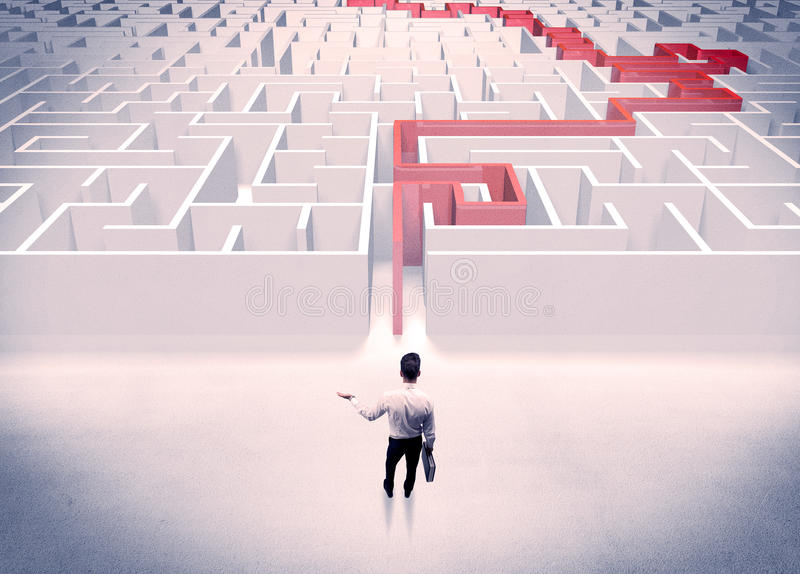 Maze solved for businessman concept. A businessman in suit giving thumbs up in front of labyrinth with red line showing the way out royalty free stock images