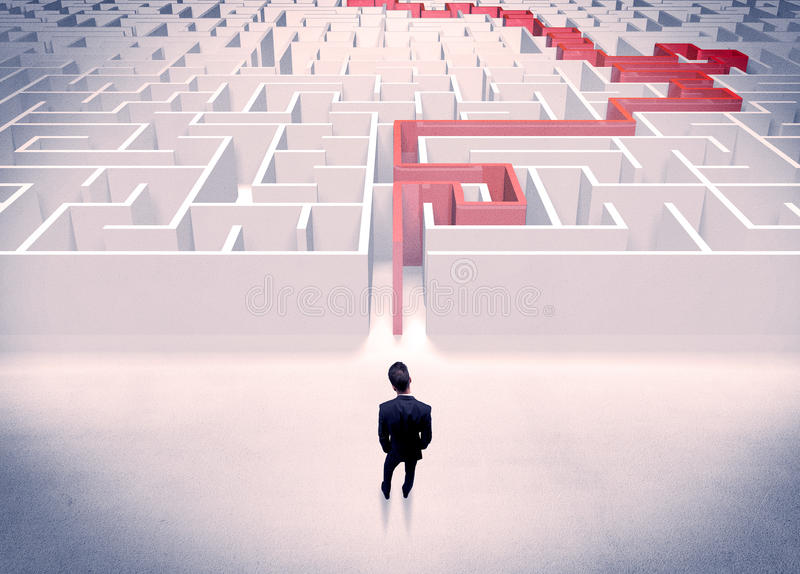 Maze solved for businessman concept. A businessman in suit giving thumbs up in front of labyrinth with red line showing the way out royalty free stock photo