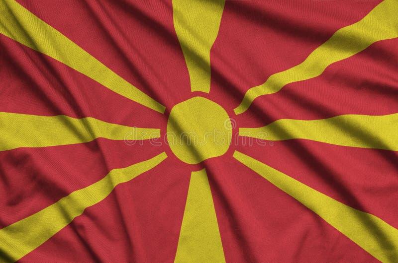 Mazedonien-Flagge wird auf einem Sportstoffgewebe mit vielen Falten dargestellt Sportteamfahne stockbild