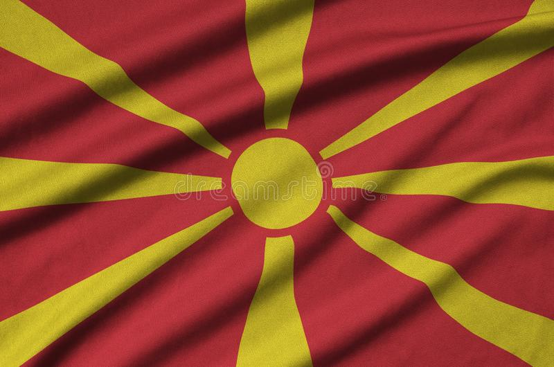 Mazedonien-Flagge wird auf einem Sportstoffgewebe mit vielen Falten dargestellt Sportteamfahne lizenzfreies stockbild