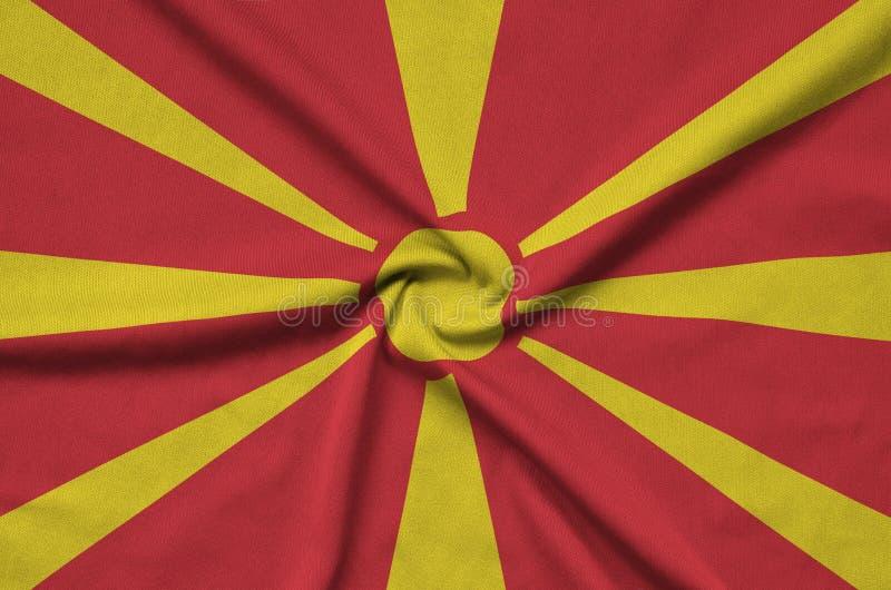 Mazedonien-Flagge wird auf einem Sportstoffgewebe mit vielen Falten dargestellt Sportteamfahne lizenzfreie stockfotos