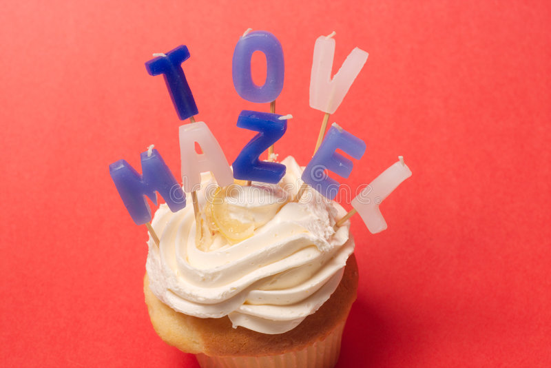 Mazel Tov candles on cupcake. Vanilla Cupcake with frosting and unlit blue and white candles spells Mazel Tov. Photographed on a red background royalty free stock photos